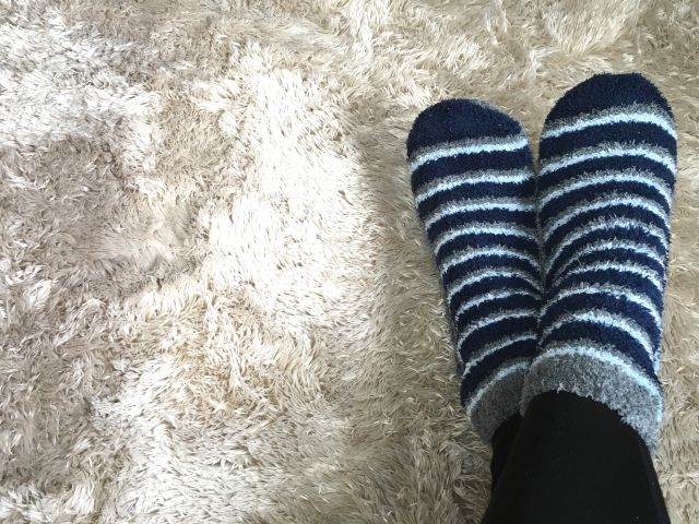 靴下を履いて寝る人の足の写真