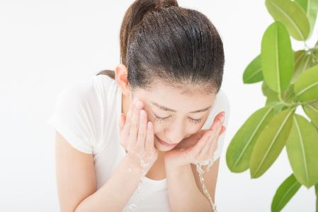 洗顔後にぬるま湯ですすいでいる女性の写真