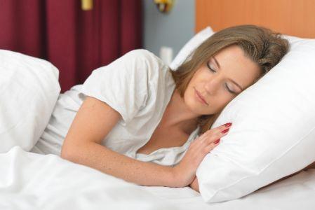 睡眠をとってお肌のターンオーバーを促進させている女性の写真