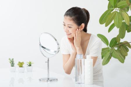 メラニンの生成を予防するスキンケアを実践する女性のイメージ写真