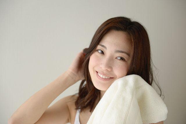 タオルでゴシゴシ顔を拭く女性の写真