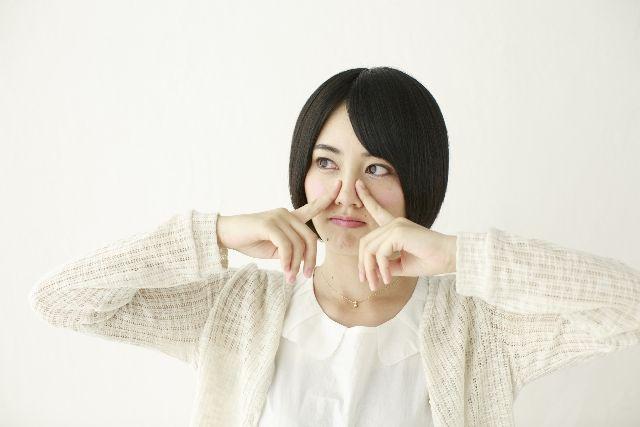 角栓を指で押しだして取りだすマッサージをしている女性の写真