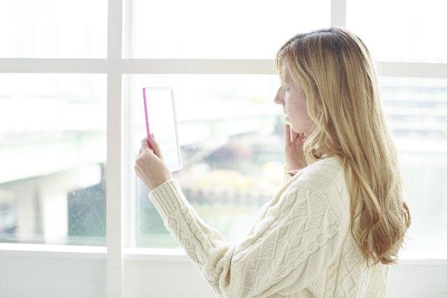 ニキビ肌に困って鏡を見る女性の写真