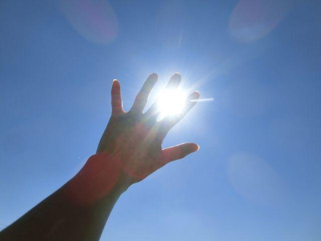 太陽光の紫外線を手で遮る写真