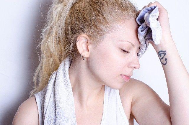 運動のし過ぎで疲労に苦しむ女性の写真