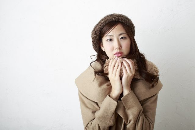 体を冷やさないようにコートを着ている女性の写真