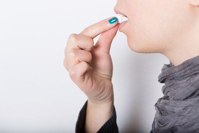 サプリメントを飲んでいる女性の写真
