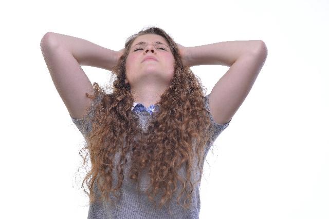 考え方のクセによって精神的な疲労に苦しむ女性の写真