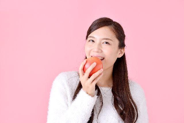 リンゴを食べる女性の写真