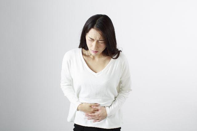牡蠣の食中毒に苦しむ女性のイメージ写真