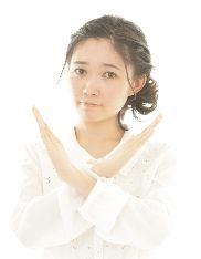 腕をバツ印をする女性の写真